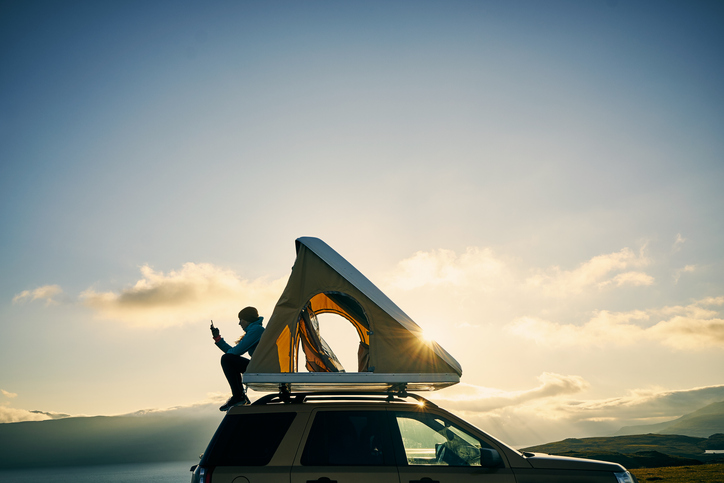 woman sitting on top of suv with a tent