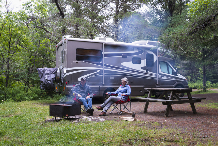 two rvers sitting in front of their camper