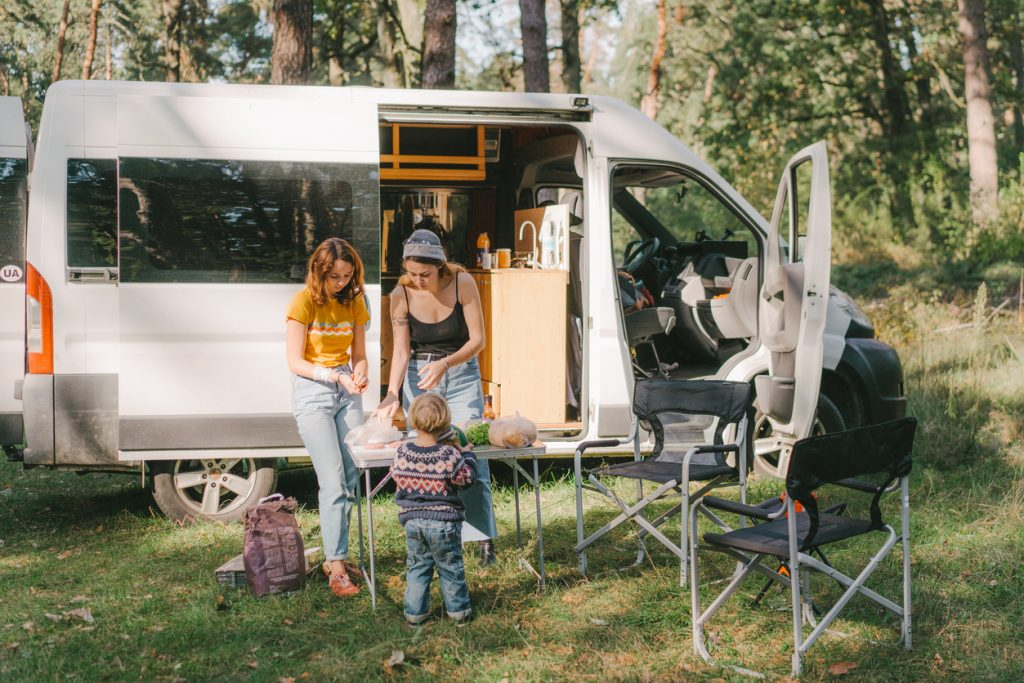 Women cook outside camper van