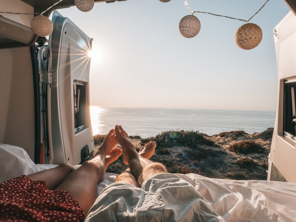 How much does van life cost? Couple sits on back of camper van